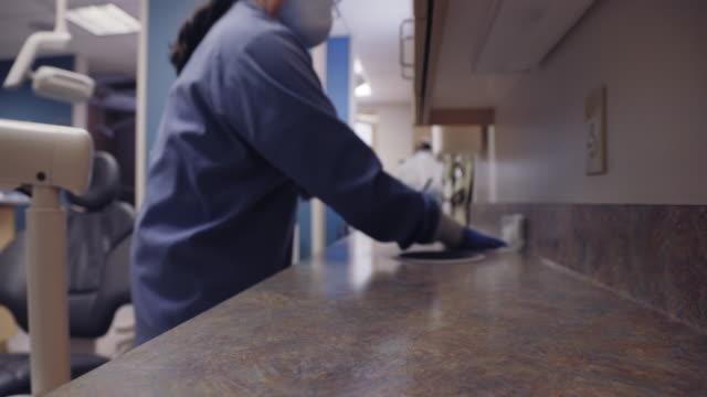 eine latina dental hygienistin in ihren fünfzigern trägt eine gesichtsmaske wischvon einem zähler und verschiedenen oberflächen um einen untersuchungsraum in einer zahnarztpraxis in vorbereitung auf den nächsten patienten - reinigen stock-videos und b-roll-filmmaterial