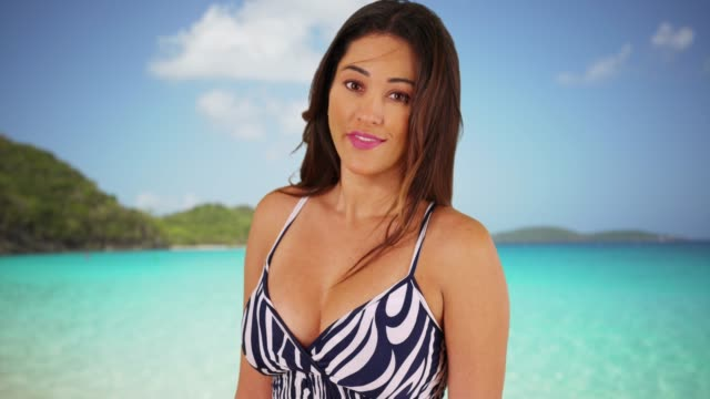 latina female standing by ocean in the caribbean, looking at camera confidently - sommerkleid stock-videos und b-roll-filmmaterial