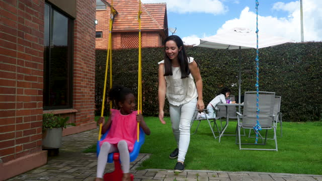 stockvideo's en b-roll-footage met latina mom is in the backyard of her house with her daughter messing her on the swing - messing about