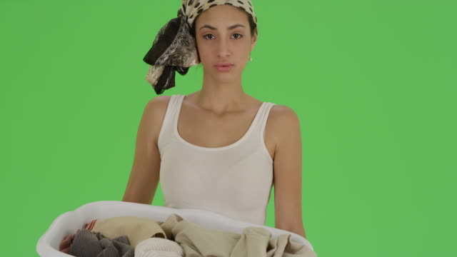 latina poses for portrait holding a laundry basket on green screen - laundry basket stock videos and b-roll footage