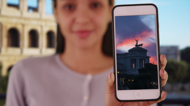 latina shows image of monumento nazionale a vittorio emanuele ii on phone. - altare della patria stock videos and b-roll footage