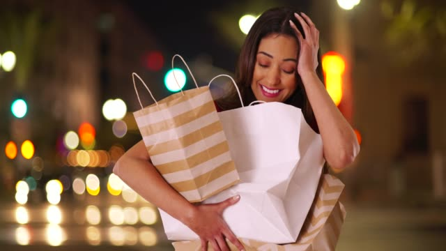 stockvideo's en b-roll-footage met latina woman carrying load of shopping bags in her arms, laughing at camera - shopaholic