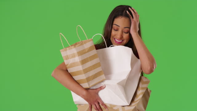 stockvideo's en b-roll-footage met latina woman carrying load of shopping bags in her arms on green screen - boodschappentas tas