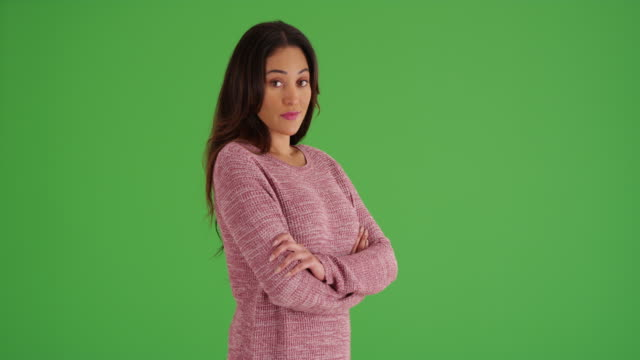 latina woman in cozy pink sweater smiling at camera on green screen - starren stock-videos und b-roll-filmmaterial