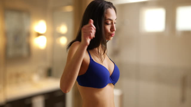 a latina woman in her lingerie acts seductively in her bathroom - bagno video stock e b–roll