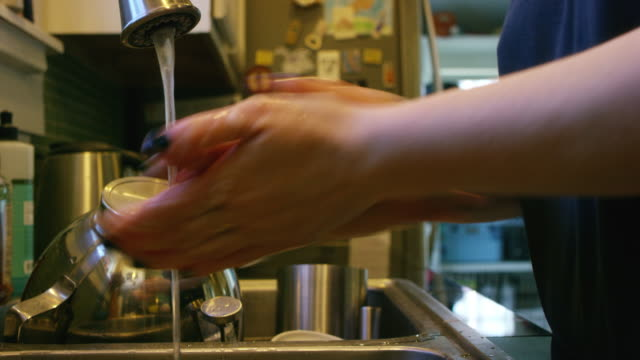 vídeos de stock e filmes b-roll de a latina young adult woman washes her hands before preparing food - pão de fermento