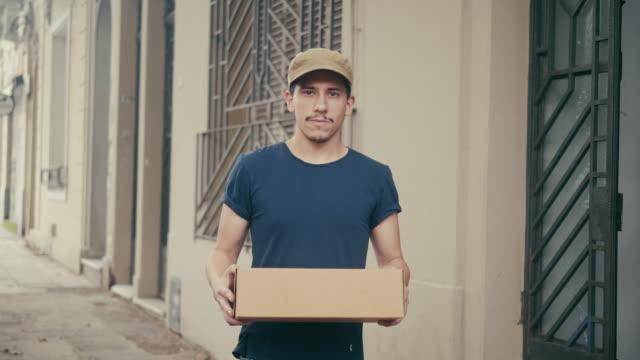 vídeos y material grabado en eventos de stock de repartidor latinoamericano con paquete - recibir