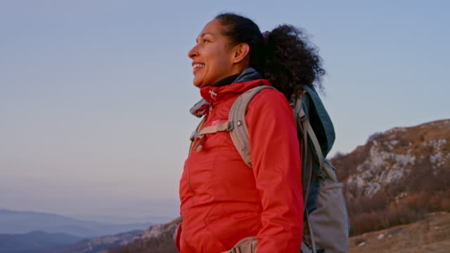 slo mo latin-american female hiker smiling as she reaches the mountain top at sunset - sustainable tourism stock videos & royalty-free footage