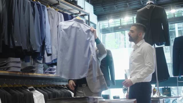 仕立て屋でシャツを選ぶラテンアメリカ人男性 - サービス業関係の職業点の映像素材/bロール
