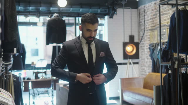 latin-american man tries on a new suit at the menswear store - clothes shop stock videos & royalty-free footage