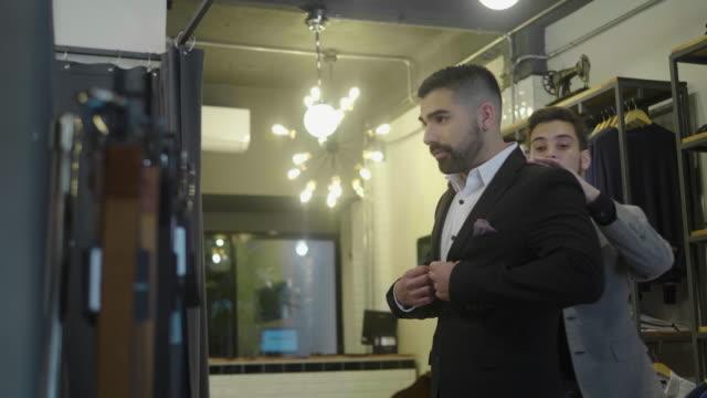 vídeos y material grabado en eventos de stock de hombre latinoamericano se prueba un traje nuevo en la tienda de ropa masculina - vestimenta de negocios