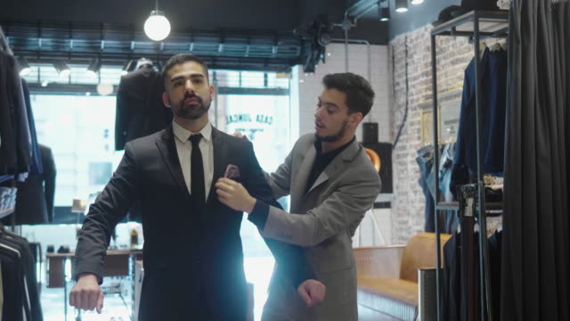 latin-american man tries on a new suit at the menswear store - 20 24 years stock videos & royalty-free footage
