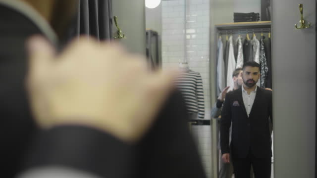 latin-american man tries on a new suit at the menswear store - suit stock videos & royalty-free footage