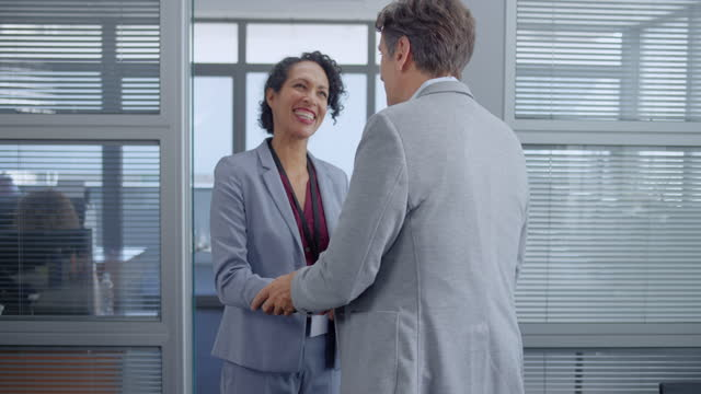 slo mo latin-american woman and caucasian man shaking hands in the office and walking to the meeting room - businesswear stock videos & royalty-free footage
