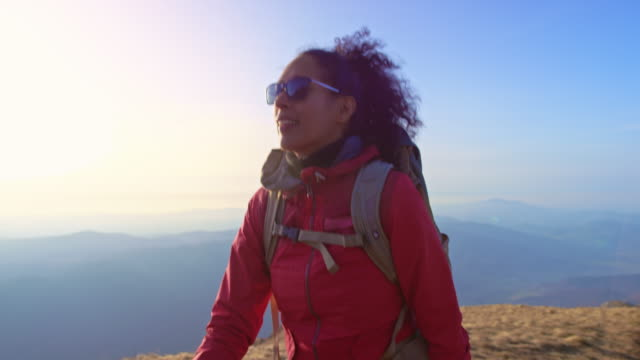 slo mo ts latin-american woman wearing sunglasses and enjoying the nature while walking up a mountain - hiking stock videos & royalty-free footage