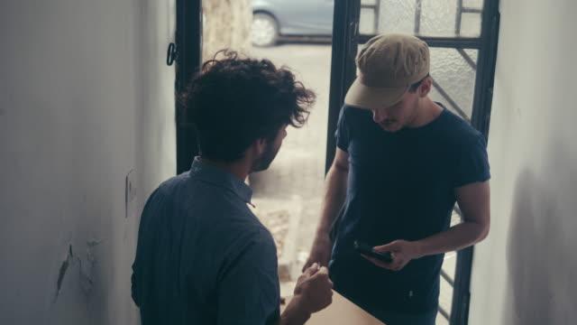 lateinamerikanische junge männliche erhält ein paket an der tür - postangestellter stock-videos und b-roll-filmmaterial