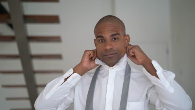 vidéos et rushes de homme africain latino s'habiller à la maison - chemise