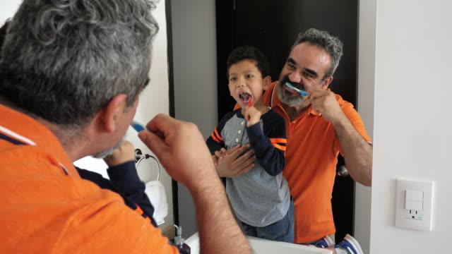 latino boy brushing teeth with father - mexican ethnicity stock videos & royalty-free footage