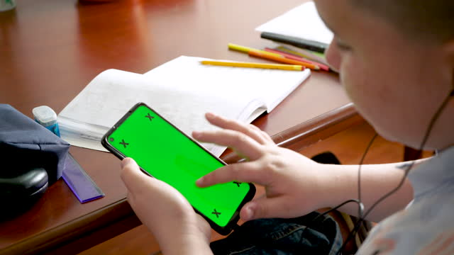 latino boy sitting at the table in his house doing homework with the help of the cell phone - 12 13 years stock videos & royalty-free footage