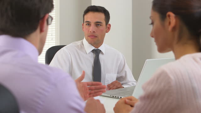 Latino businessman advising couple