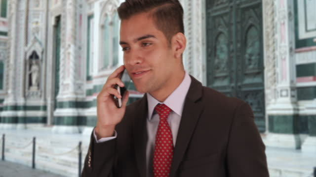 latino businessman talking with client on cellphone duomo di firenze in florence - etnia latino americana video stock e b–roll