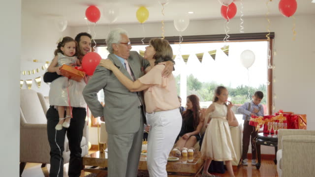 vídeos de stock e filmes b-roll de latino family made up of children, grandchildren, grandparents, popes, celebrate the birthday mom and grandmother, the compliment kisses her husband while he gives his gift and on the one hand his son comes with his little granddaughter who also gives his - objeto decorativo