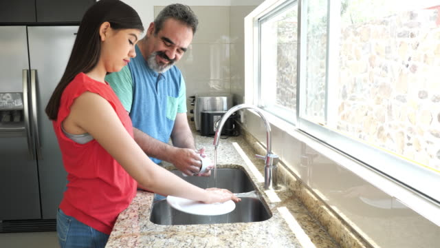 latino father and daughter washing dishes - lavori di casa video stock e b–roll