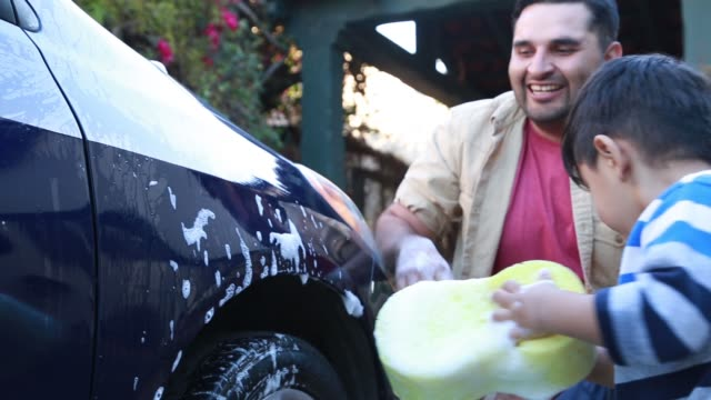 latino father and son washing car together - driveway stock videos & royalty-free footage