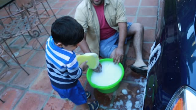 Latino Father and Son Washing Car Together