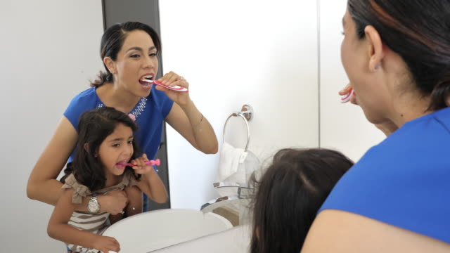 latino girl brushing teeth with parent - brushing teeth stock videos & royalty-free footage