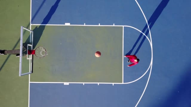 vídeos de stock e filmes b-roll de latino guy shooting basketball on the court in usa in summer - drone footage - ténis calçado desportivo