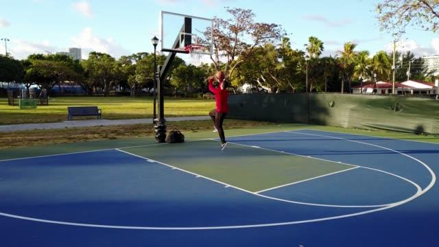 vidéos et rushes de mec latino tir basket sur la cour aux etats-unis en été - miami