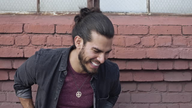 latino handsome man laughing against a red brick wall - barba peluria del viso video stock e b–roll