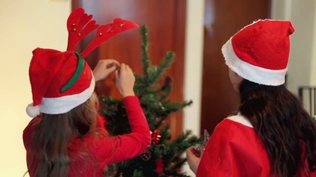 Latino Lifestyle. Girls preparting the Christmas tree.
