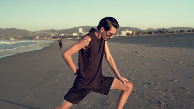 Latino Lifestyle. Skinny, not well trained, young Latino / Hispanic man with tattoo make stretching exercise on the beach, when the girl jogging in the background