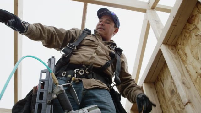 vídeos de stock e filmes b-roll de a latino man in his forties standing on construction framing and uses a level to make sure the wall is level in winter under an overcast sky - armação de construção
