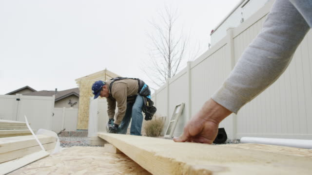 a latino man in his forties uses a circular saw to cut a wooden plank as another person secures the board on a construction site in winter under an overcast sky - recinzione video stock e b–roll