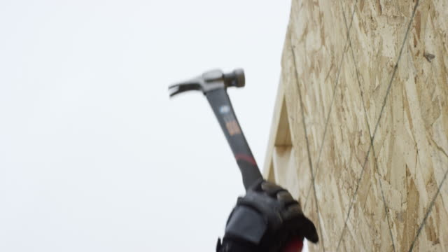 a latino man in his forties uses a hammer to secure a sheet of particle board in place at a construction site in winter under an overcast sky - building contractor stock videos & royalty-free footage