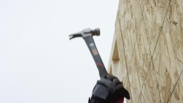 vídeos y material grabado en eventos de stock de un hombre latino en su años cuarenta utiliza un martillo para asegurar una lámina de aglomerado en el lugar en un sitio de construcción en invierno bajo un cielo nublado - gorra de béisbol