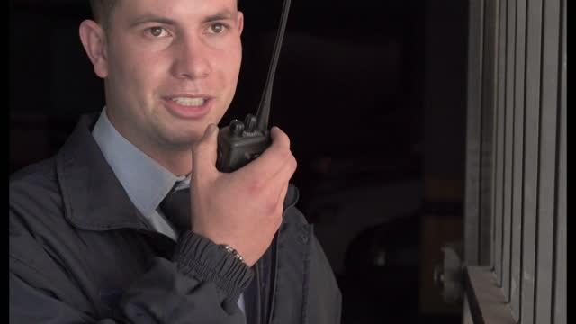 latino mann wachmann eines gebäudes, ist auf dem parkplatz geben eine information im radio - portable information device stock-videos und b-roll-filmmaterial