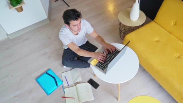 ラテン系の男性は、彼の家の快適さから勉強します - 記事点の映像素材/bロール