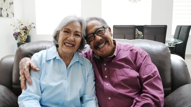 ラテン系シニアカップルが抱き合い、ソファに座る - 年金点の映像素材/bロール