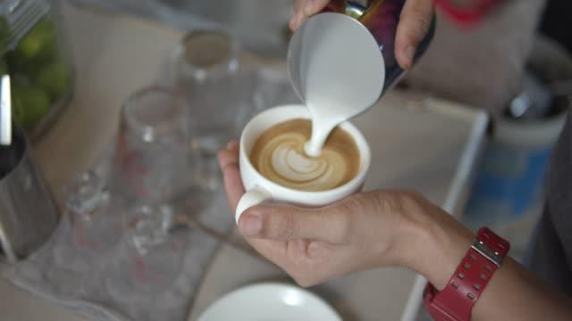 vídeos de stock e filmes b-roll de latte art making,slow motion - primeiríssimo plano