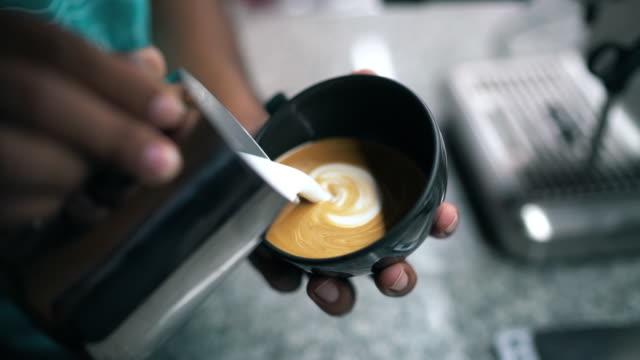 latte art, milch eingießen von einem barista. - art stock-videos und b-roll-filmmaterial