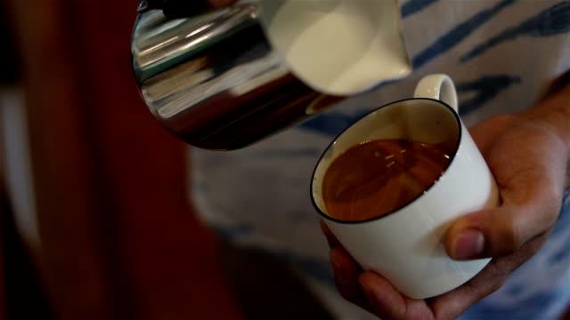 vídeos de stock, filmes e b-roll de latte art, leite derramando por um barista - xícara de café