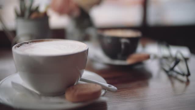ラテコーヒーは飲むのを待つ - カプチーノ点の映像素材/bロール