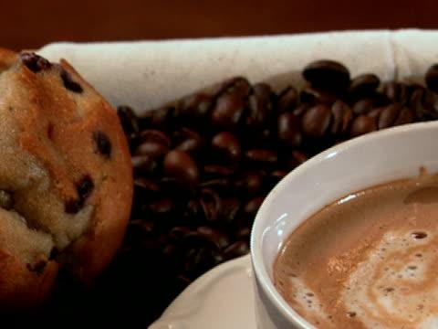 ラテのベッドの上のコーヒー豆 - マフィン点の映像素材/bロール