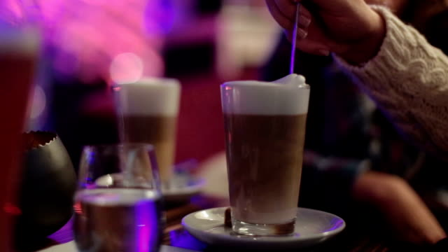 Latte on the table being stirred by a female hand - side view