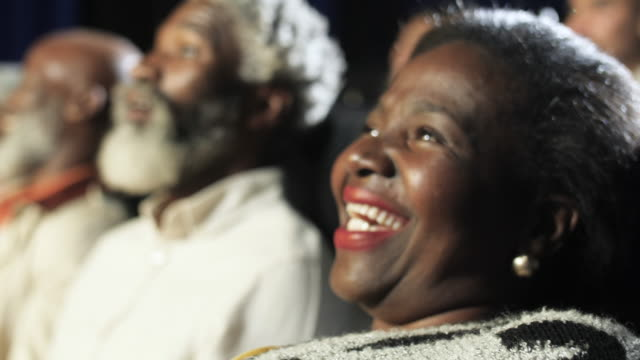 laughing african american woman in movie theatre, close up - film industry stock videos & royalty-free footage