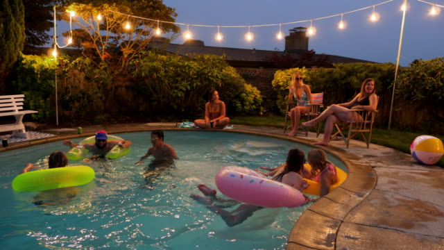 MS Laughing and smiling friends hanging out together during backyard pool party on summer evening